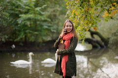 Милая девушка в ярком красном шарфе идя в парк осени Стоковое фото RF