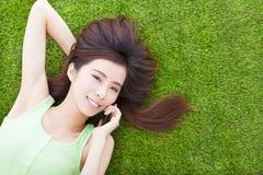 Милая девушка лежа вниз на луге и говоря smartphone Стоковая Фотография RF