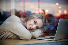 Милая девушка лежа на таблице с компьтер-книжкой в кафе Стоковые Фото