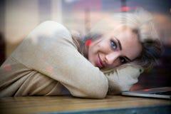Милая девушка лежа на таблице с компьтер-книжкой в кафе Стоковые Изображения