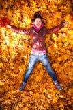 Милая девушка лежит в желтых листьях Стоковое Фото