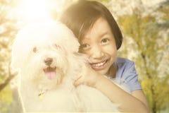 Милая девушка держа ее щенка на парке Стоковые Изображения
