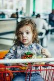 Милая девушка держа контейнеры с здоровой едой в оружиях сидя в магазинной тележкае стоковые изображения