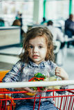 Милая девушка держа контейнеры с здоровой едой в оружиях сидя в магазинной тележкае стоковое изображение