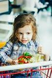 Милая девушка держа контейнеры с здоровой едой в оружиях сидя в магазинной тележкае стоковое изображение rf
