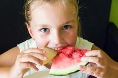 Милая девушка есть арбуз и дыню Стоковые Изображения RF