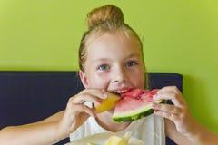 Милая девушка есть арбуз и дыню Стоковое Изображение