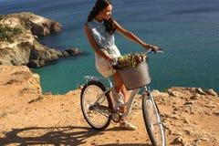 Милая девушка ехать велосипед вдоль морского побережья Стоковые Фотографии RF
