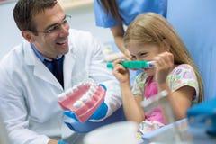 Милая девушка делает шутку с ее дантистом в зубоврачебной клинике стоковые фото