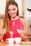 Милая девушка женщины добавляя сахар к чаю или кофе стоковые изображения