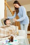Милая девушка заботя для больного парня Стоковое Фото