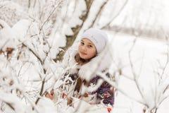 Милая девушка играя в лесе зимы Стоковая Фотография