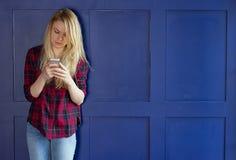 Милая девушка играя с ее телефоном Стоковые Изображения