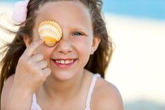 Милая девушка играя с раковиной на пляже. Стоковая Фотография RF