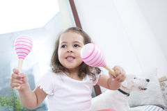 Милая девушка играя с maracas пока сидящ около собаки дома Стоковые Фотографии RF