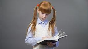 Милая девушка имбиря читает книгу акции видеоматериалы