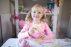 Милая девушка имея чай пока играющ при от установленная кухня игрушки Стоковые Фотографии RF