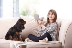 Милая девушка используя цифровую таблетку Стоковое Изображение