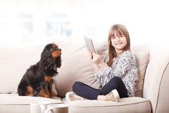 Милая девушка используя цифровую таблетку Стоковая Фотография