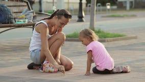 Милая девушка и ее чертеж матери с мелом на тротуаре сток-видео