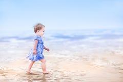 Милая девушка малыша в голубом платье идя на пляж стоковая фотография