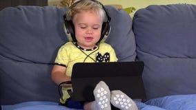 Милая девушка малыша с наушниками используя таблетку и слушать к музыке сток-видео