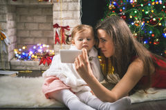 Милая девушка малыша украшая рождественскую елку шарики красные Стоковая Фотография