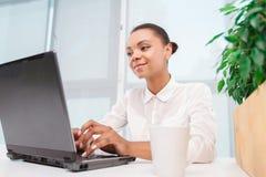 Милая девушка мулата работая на компьютере Стоковое Фото