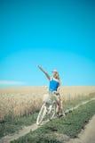 Милая девушка на велосипеде с корзиной в пшенице лета Стоковые Фото