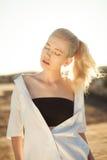 Милая девушка на крыше стоя в солнечном свете на заходе солнца Стоковые Изображения