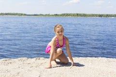 Милая девушка на речном береге в розовом купальнике Стоковые Фото