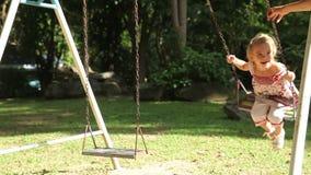 Милая девушка на seesaw в парке Мама и дочь тратят время в парке видеоматериал