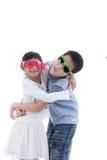 Милая девушка обнимая азиатского мальчика изолированного на белизне Стоковое Изображение RF