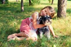 Милая девушка обнимая ее собаку стоковые изображения rf