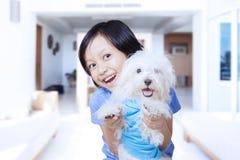 Милая девушка обнимая ее щенка дома Стоковое Изображение