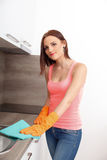 Милая девушка очищает кухню Стоковые Фотографии RF