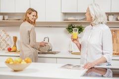Милая девушка помогая ее родителю в кухне стоковое фото