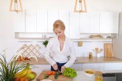 Милая девушка подготавливая салат свежих овощей на разделочной доске Стоковое Фото