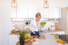 Милая девушка подготавливая салат свежих овощей на разделочной доске Стоковые Фотографии RF