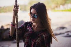 Милая девушка представляя на пляже Она держит веревочку и смотреть далеко Совершенное фото для магазина моды стоковое изображение