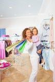 Милая девушка при ее мать держа хозяйственные сумки Стоковое Изображение