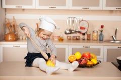 Милая девушка при шляпа шеф-повара держа большую деревянную ложку Стоковая Фотография RF