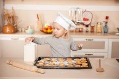 Милая девушка при шляпа шеф-повара подготавливая печенья внутри Стоковое Изображение