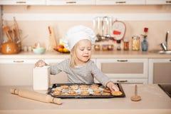 Милая девушка при шляпа шеф-повара подготавливая печенья Стоковое Фото