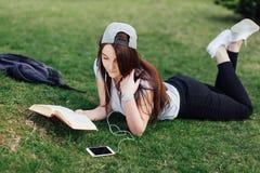 Милая девушка прочитала книгу и слушает музыка на парке Стоковые Фотографии RF