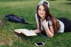 Милая девушка прочитала книгу и слушает музыка на парке Стоковая Фотография RF