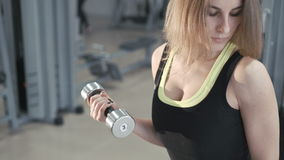 Милая девушка разрабатывая с гантелями в спортзале в 4K акции видеоматериалы