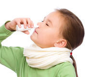 Милая девушка распыляя ее нос стоковые изображения rf