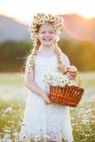 Милая девушка ребенка на поле стоцвета с корзиной цветков Стоковая Фотография RF