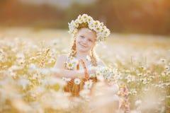 Милая девушка ребенка на поле стоцвета с корзиной цветков Стоковые Изображения
